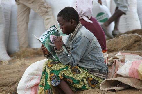 Farmer in Malawi reading a farmer's magazine