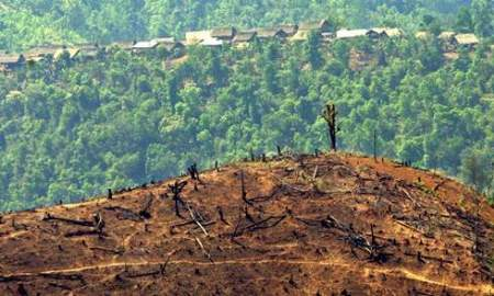 epa00182685 A small village where rice and opium farmers live is seen behind a large hill which has been cleared of timber by slash and burn methods ready for agriculture, in north-eastern Myanmar (Burma), close to the Chinese border, Monday 26 April 2004. Unchecked logging fuelled by the huge growth in the Chinese economy has taken its toll on the area. Deforestation is acute in Myanmar as a consequence of timber exploitation and poor agricultural methods and it is one of the least environmentally protected countries in South East Asia. Myanmar supplies 60 per cent of the world's teak wood consumption, and derives nearly 10 percent of it's foreign income from timber exports. EPA/BARBARA WALTON